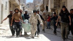 Des civils syriens évacuent des personnes blessées dans les bombardements, à Alep, le 30 mai 2016.