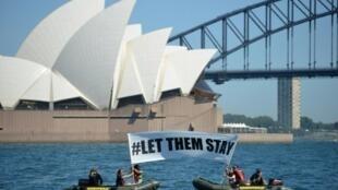 """ناشطون من """"غرين بيس"""" يرفعون لافتة كتب عليها """"اتركوهم يبقون"""""""