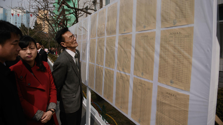 Los votantes norcoreanos observan las listas electorales mientras hacen fila para depositar sus papeletas en un centro de votación, en Pyongyang, el 10 de marzo de 2019.