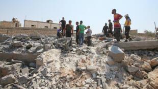 Des Syriens inspectent les dégâts causés par un raid aérien sur le village de Deïr Charki, dans la province d'Idleb, le 17août2019.