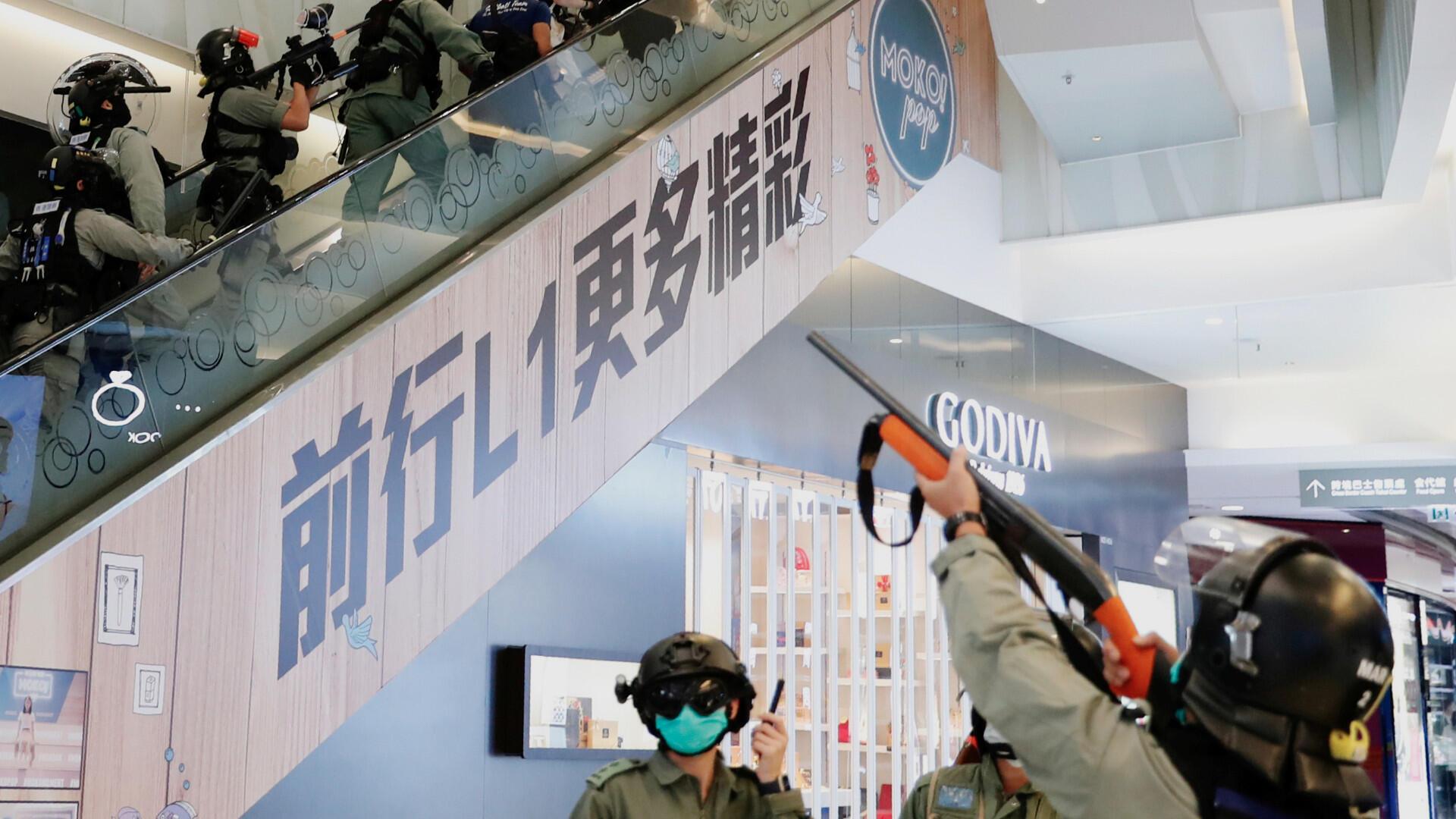 La policía antidisturbios apunta con su arma de gas pimienta dentro de un centro comercial mientras dispersan a los manifestantes antigubernamentales durante un mitin, en Hong Kong, China, el 10 de mayo de 2020.