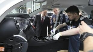 Russian President Vladimir Putin (left) and German economy minister Peter Altmaier inspect a car made at the new Mercedes-Benz plant