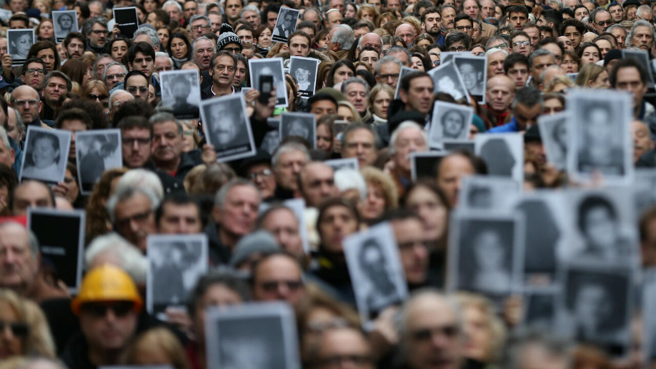 Familiares de las víctimas del atentado a AMIA sostienen fotografías de los fallecidos en el ataque producido en 1994, durante el 25° aniversario de los hechos. Buenos Aires, Argentina, el 18 de julio de 2019.