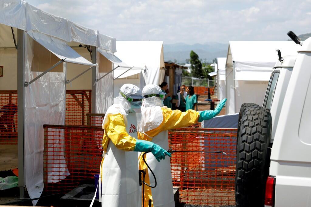 Trabajadores de la salud vestidos con trajes protectores mientras desinfectaban una ambulancia que transportaba a un paciente sospechoso de ébola al recién construido centro de tratamiento en Goma, República Democrática del Congo, el 4 de agosto de 2019.
