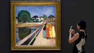 """Une femme devant le tableau d'Edvard Munch, """"Les Filles sur le pont"""", à New York le 4 novembre 2016."""