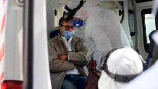 فريق طبي يتابع مريضاً مصاباً بفيروس كوفيد-19 داخل سيارة إسعاف في العاصمة تونس في 6 نيسان/أبريل 2020