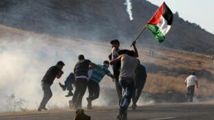 فلسطينيون يحملون جريحا سقط بنيران الجيش الإسرائيلي في الضفة الغربية في 1 آب/ أغسطس 2015
