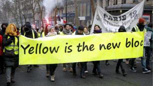 Los 'chalecos amarillos' llevan una pancarta en la décima manifestación del movimiento. París, 19 de enero de 2019.