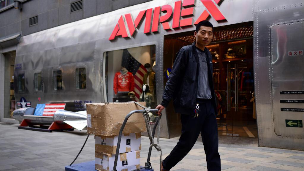 رجل صيني يجر عربة قرب مقعد على شكل قنبلة بألوان العلم الأمريكي في بكين