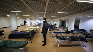 A security guard stands by beds installed inside the Palais des Festivals on March 24, 2020 as Cannes Mayor David Lisnard decided to open a part of the palace to welcome the needy and homeless during a lockdown in France intended to contain the coronavirus outbreak.