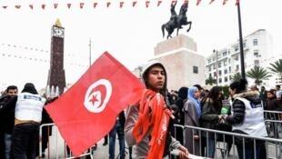 طفل تونسي حاملا علم بلاده في 14 كانون الثاني/يناير 2017