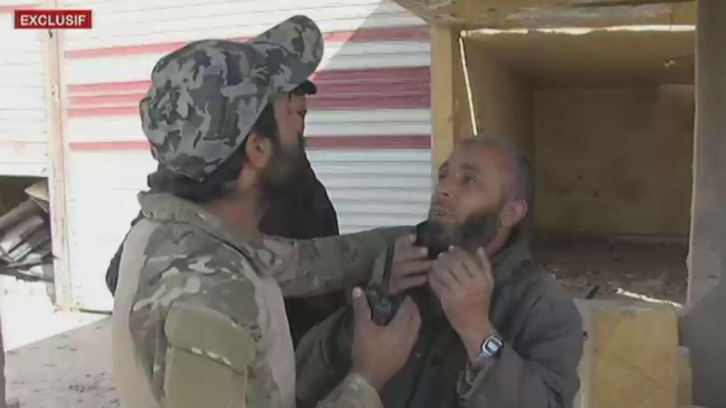 Un combattant des FDS interroge un homme dans un village à proximité de la frontière irako-syrienne en Syrie, le 20 novembre. Il sera relâché par la suite.