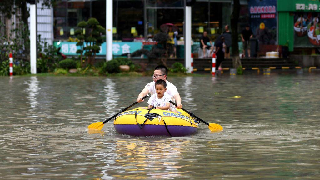 Un hombre rema un kayak inflable con un niño en una calle inundada después de que el tifón Lekima golpeara Wenling, provincia de Zhejiang, China , el 10 de agosto de 2019.