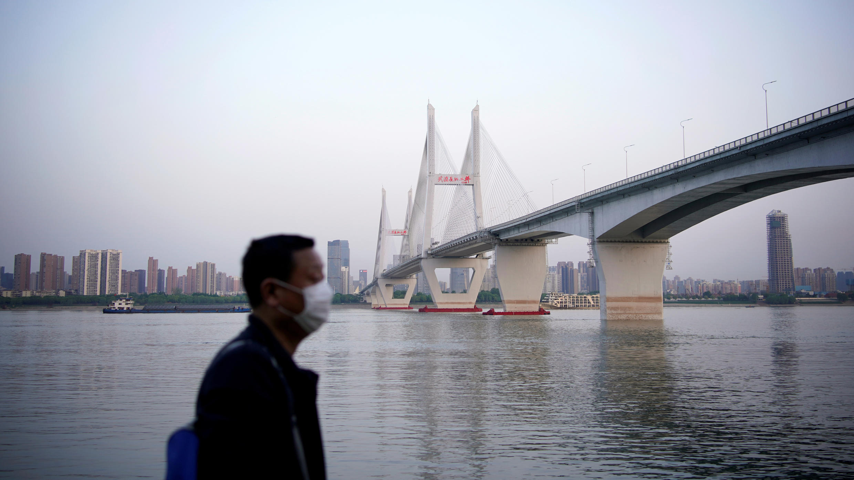 Un hombre con una mascarilla pasea cerca al río Yangtze en Wuhan, China, el 15 de abril de 2020.