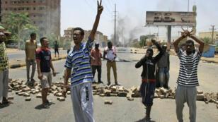 Des manifestants chantent des slogans contre le régime devant le quartier général de l'armée, à Khartoum, le 3 juin 2019.