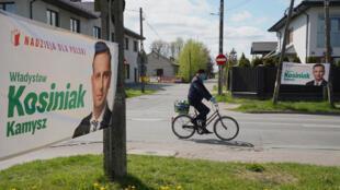 سائق دراجة هوائية يمر أمام لافتة مرشح المعارضة للانتخابات الرئاسية البولندية قرب وارسو في 30 نيسان/إبريل 2020