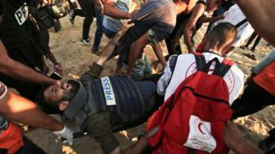 El camarógrafo palestino Atia Hijazi es llevado a una ambulancia luego de recibir un disparo en la playa cerca de la frontera marítima con Israel, en el norte de la Franja de Gaza, durante una manifestación para pedir el levantamiento del bloqueo israelí en el enclave palestino costero, el 10 de septiembre de 2018.