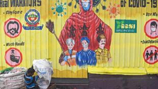 Un trapero trabaja bajo un mural decicado a los trabajadores en primera línea de la lucha contra la COVID-19 el 22 de julio de 2020 en un vertedero de basura de Nueva Delhi