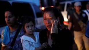 Una mujer, parte de un caravana de migrantes centroamericanos, es escoltada en una furgoneta por agentes del Instituto Nacional de Migración (INM), después de ser detenida en un punto de control en las afueras de Tapachula, México, el 19 de mayo de 2019.
