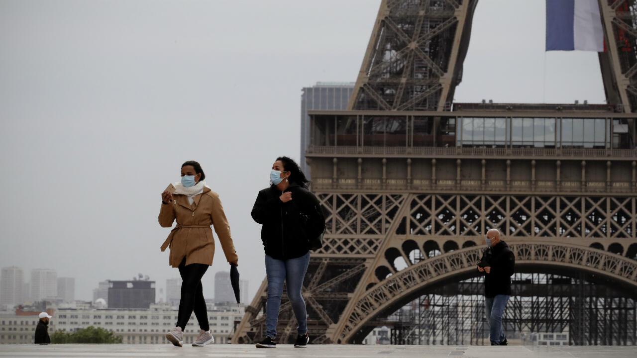 مواطنون يمشون بالقرب من برج إيفل في اليوم الذي تبدأ فيه فرنسا تخفيف إجراءات الحجر الصحي. 11 مايو/أيار 2020.
