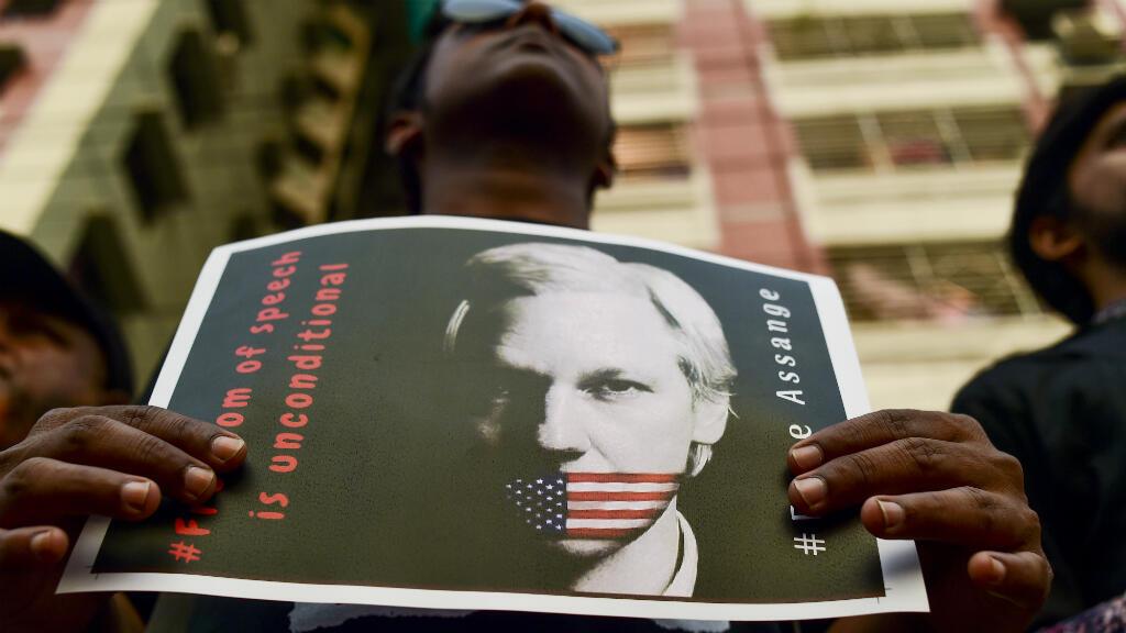 """En esta foto de archivo tomada el 23 de abril de 2019, un activista sostiene un cartel junto a otros mientras forma una cadena humana que reclama la libertad del fundador de """"WikiLeaks"""" Julian Assange, en Daca, Bangladesh, el 23 de abril de 2019."""