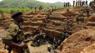 Un combattant de l'Union des patriotes congolais controle une mine d'or dans la région d'Ituri, en RDC, le 18 juin 2003.