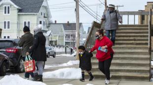 أشخاص يغادرون بعد تلقي اللقاح في مدرسة سنترال فولز الثانوية في ولاية رود آيلاند في 13 شباط/فبراير 2021.