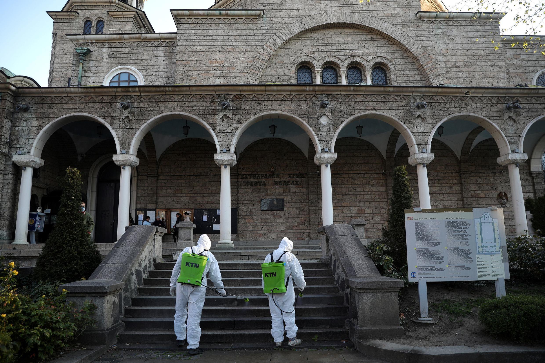 Des travailleurs pulvérisant du désinfectant à l'extérieur de l'église Sainte Nedelya, à la suite de l'épidémie de coronavirus (COVID-19), avant les services orthodoxes du dimanche des Rameaux à Sofia, Bulgarie, le 11 avril 2020.