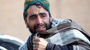 رجل أفغاني يبكي على جثة أحد ضحايا الغارة الجوية الجمعة في منطقة سخرود بمقاطعة نانجرهار.