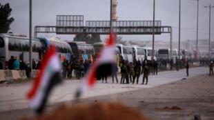 A pesar de los bombardeos, un convoy de autobuses transportará a los combatientes rebeldes y sus familiares fuera de los límites de la ciudad de Harasta, en el suburbio oriental de Ghouta