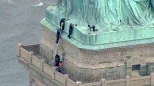 Esta imagen fija tomada del video cortesía de PIX11 News en Nueva York muestra a la policía hablando con la mujer que trepó a la base de la Estatua de la Libertad el 4 de julio de 2018.