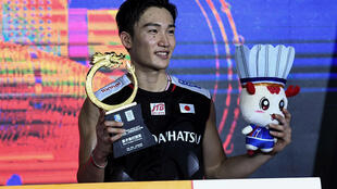 Japan's Kento Momota celebrates with the trophy after winning the China Open men's singles final in 2019 in Changzhou