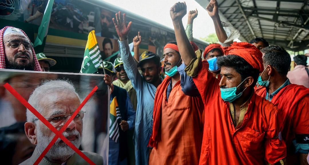 Simpatizantes del partido gobernante Tehreek-e-Insaf de Pakistán sostienen fotografías del primer ministro de la India, Narendra Modi, mientras gritan consignas durante una marcha para mostrar su solidaridad con Cachemira. Karachi, Pakistán, el 5 de agosto de 2020.