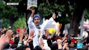 La photographie de Wadii Jelassi tenant une cage lors d'une mobilisation à Tunis, le 14 janvier 2011, a fait le tour du monde.