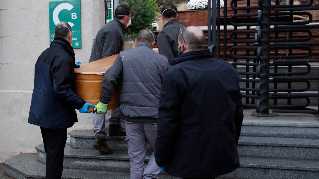 Un grupo de operarios portan un ferétro en el cementerio de Sant Gervasi, en Barcelona, España.