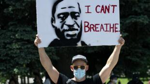 متظاهر يرفع صورة جورج فلويد في دنفر في 30 أيار/مايو 2020