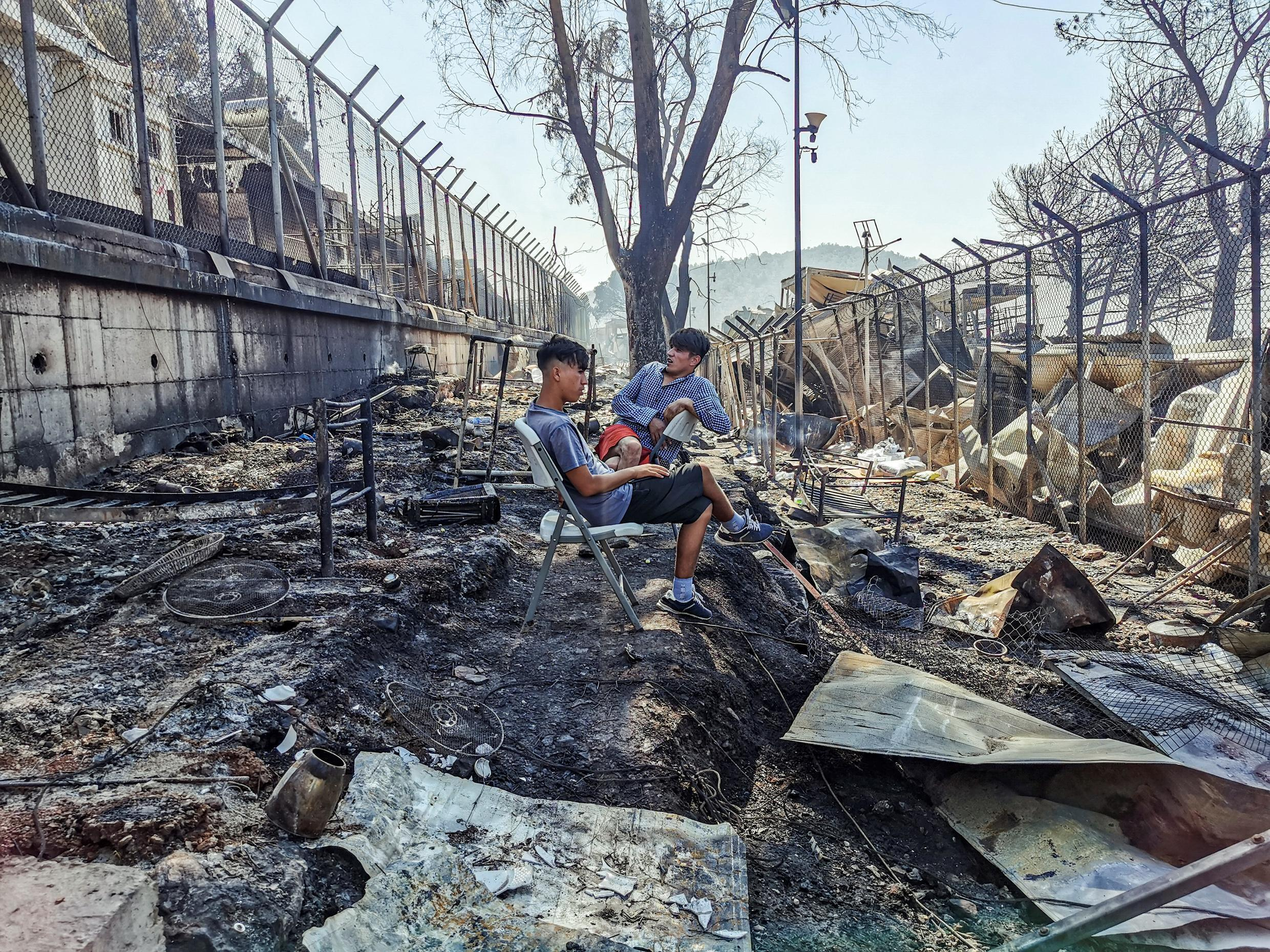 Migrants sit inside the burnt Moria Camp on the Greek island of Lesbos on September 9, 2020, after a major fire.