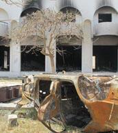 "A charred car carcass lies belly-up outside Gaddafi's ruined ""Katiba""."