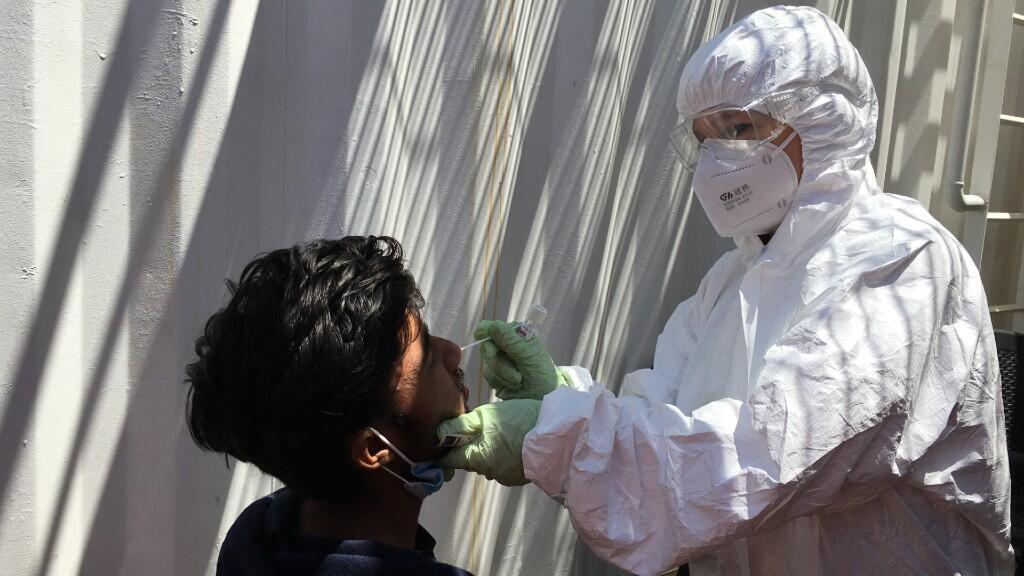 Un trabajador de la salud italiano hace una prueba de Covid-19 a un migrante rescatado en el Mediterráneo a bordo del 'Ocean Viking' el 5 de julio de 2020.