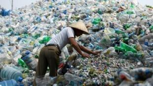 Un Vietnamien devant une montagne de bouteilles plastique à Hanoi le 4 juin 2018