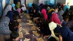 نازحون أفغان يتناولون الفطور بعد وصولهم من محافظة جاغوري في غزنة هرباً من المعارك الدائرة بين طالبان وقوات الأمن الأفغانية في ولاية غزنة في 12 ت2/نوفمبر 2018
