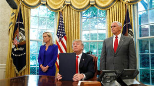 El presidente estadounidense, Donald Trump, con su orden ejecutiva sobre política de inmigración después de firmarla junto a la Secretaria de Seguridad Nacional, Kirstjen Nielsen, y el vicepresidente Mike Pence en la Oficina Oval en la Casa Blanca en Washington, EE. UU., El 20 de junio de 2018.