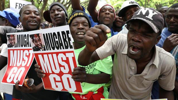 Manifestantes piden que el presidente de Robert Mugabe renuncie, al otro lado de la carretera del parlamento en Harare, Zimbabue, el 21 de noviembre de 2017.