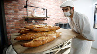 "French baker Sylvain Cabane, wearing a protective face mask, takes a tray of baguettes out of the oven at the bakery ""Ma Boulangerie"" in Vertou, near Nantes on March 17, 2020, as France faces the spread of the novel coronavirus."