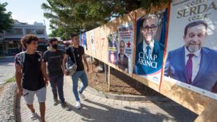 """شباب قبارصة يمرون أمام الملصقات الانتخابية في كيرينيا في """"جمهورية شمال قبرص التركية"""" التي لا تعترف بها سوى أنقرة، شمال العاصمة القبرصية المقسمة نيقوسيا، في 9 تشرين الأول/أكتوبر 2020"""