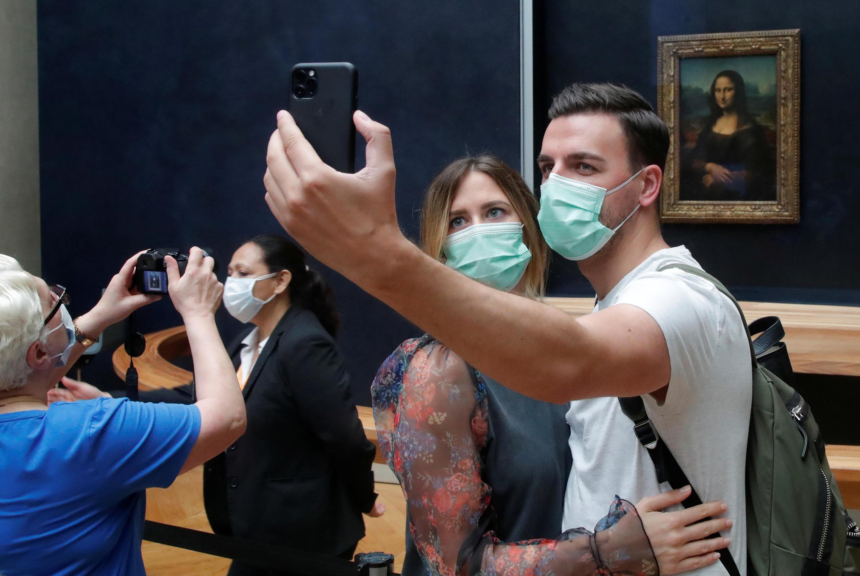 Des visiteurs masqués font un selfie devant La Joconde, au musée du Louvre, à Paris, le 6 juillet 2020.