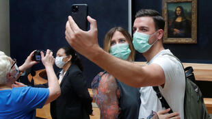 "Visitors, wearing protective face masks, make a selfie in front of the ""Mona Lisa"" (La Joconde) by Leonardo Da Vinci at the Louvre museum in Paris as the museum reopens its doors to the public after almost 4-month closure due to the coronavirus disease (COVID-19) outbreak in France, July 6, 2020."