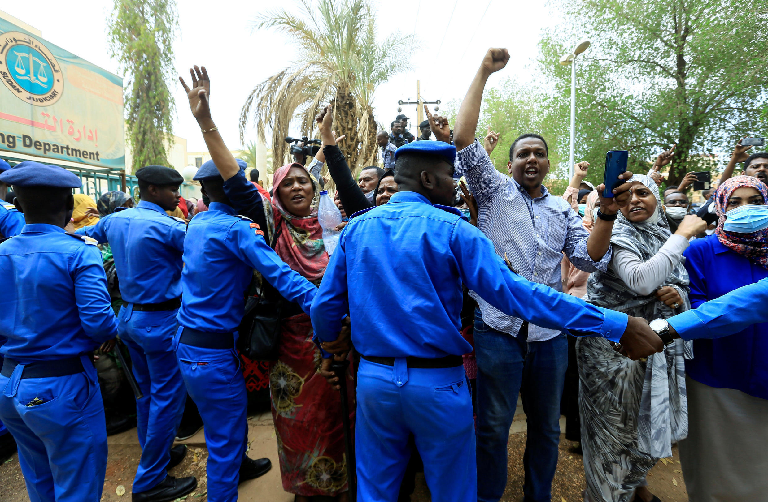 Sudanese police officers control civilians as they chant slogans outside the court during the new trial against ousted President Omar al-Bashir and some of his former allies on charges of leading a military coup that brought the autocrat to power in 1989 in Khartoum, Sudan July 21, 2020.