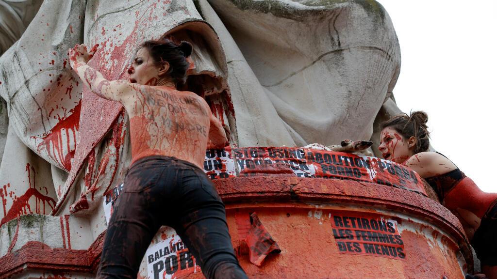 """Una mujer con el mensaje escrito en su espalda, """"No se debe vender carne"""" mientras grita a la estatua en la Plaza de la República durante una protesta para resaltar la disparidad salarial entre mujeres y hombres, en París, Francia, el 8 de marzo de 2019."""