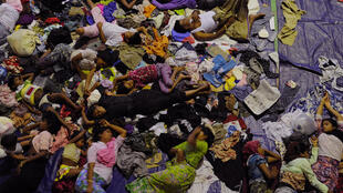 A group of rescued mostly Rohingya migrants from Myanmar and Bangladesh sleep in Aceh province on May 12, 2015 after Indonesian rescuers found their boat stranded.